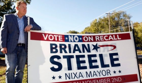 Mayor Brian Steele poses next to one of his campaign signs in Nixa, Missouri, on Oct. 21.
