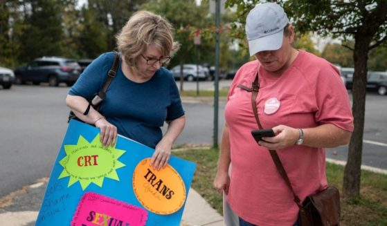 Protesters stand outside a Loudoun County Public Schools board meeting in Ashburn, Virginia, on Oct. 12.