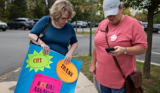 Protestors stand outside a Loudoun County Public School board meeting in Ashburn, Virginia, on Tuesday.