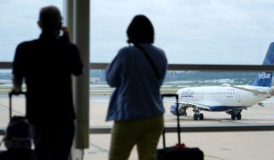 Travelers watch a JetBlue Airways aircraft taxi at Ronald Reagan Washington National Airport in Arlington, Virginia.
