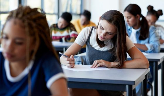 A stock photo shows students sitting in class and writing at their desks.