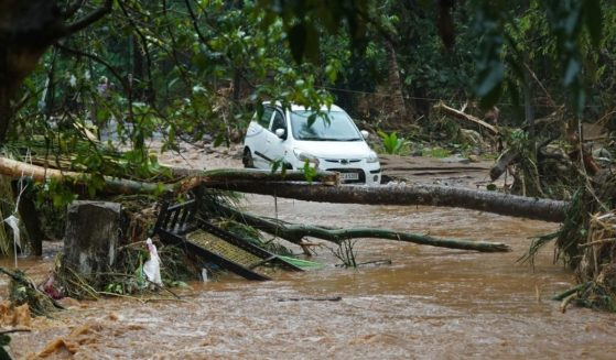 A car is stuck in murky water due to flash floods at Thodupuzha in India's Kerala state on Saturday.
