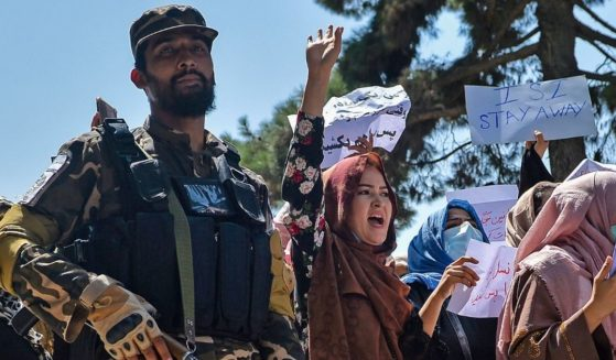 Afghan women march next to a Taliban fighter during an anti-Pakistan demonstration near the Pakistan embassy in Kabul on Sept. 7.
