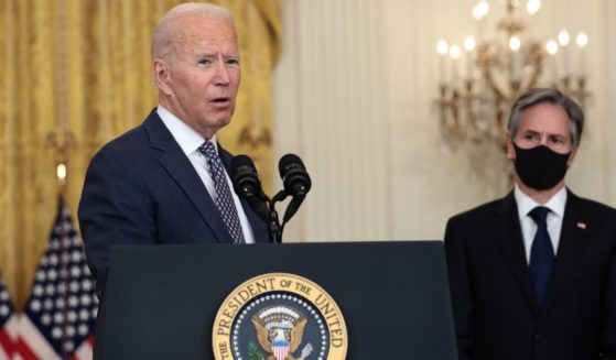 President Joe Biden stands with Secretary of State Antony Blinken while delivering remarks from the East Room of the White House in Washington, D.C., on Aug. 20.