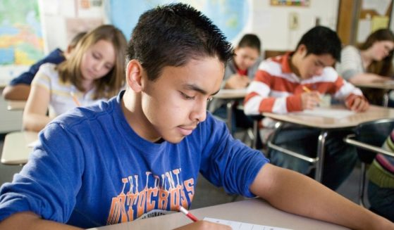 A stock photo shows students in the classroom working at their desks.