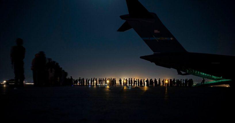 U.S. Air Force crew members prepare to load evacuees aboard an Air Force C-17 Globemaster III aircraft in Kabul, Afghanistan, on Aug. 21.