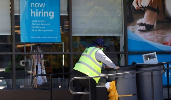 """A worker pushes a cart past a """"Now Hiring"""" sign outside of a Ross store in Sausalito, California, on June 3."""