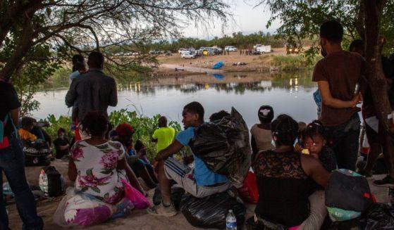 Haitian immigrants wait to cross the Rio Grande into Del Rio, Texas, on Sept. 23, 2021.
