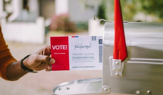 A man puts an absentee ballot in a mailbox in the above stock image.