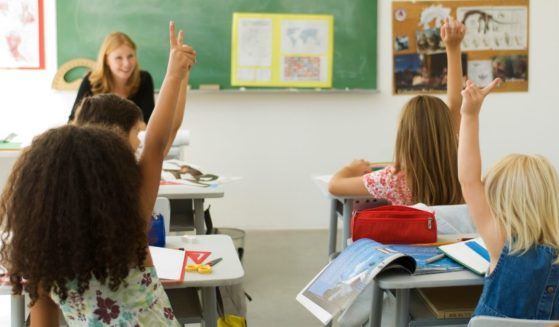 Children raise their hands in a classroom in this stock image.
